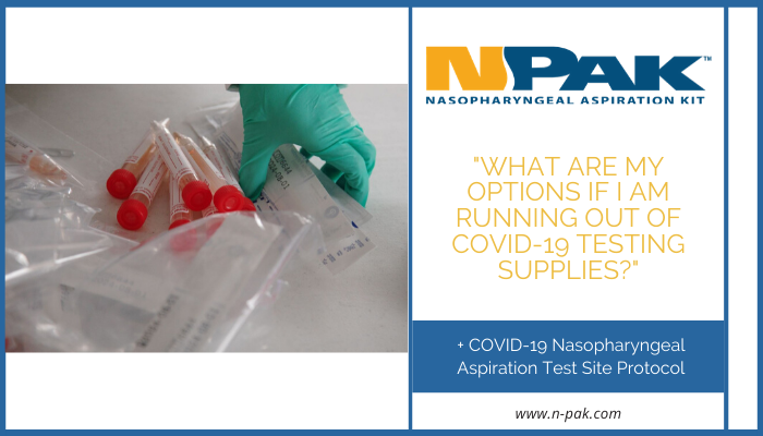 A pile of COVID-19 testing supplies. Someone is reaching their hand in the pile to pick up the tubes.